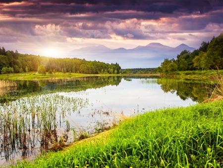 Fantastic landscape with lake and dramatic sky. Overcast sky. Carpathian, Ukraine, Europe. Beauty world.