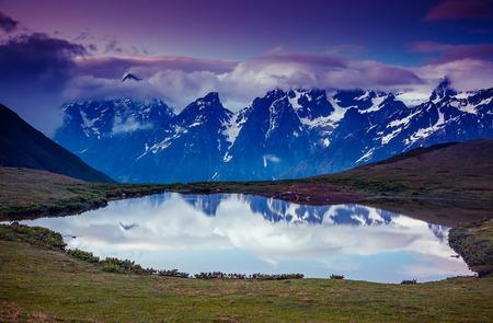 majestic mountain: Fantastic landscape with lake Koruldi and overcast sky at the foot of  Mt. Ushba. Upper Svaneti, Mestia, Georgia, Europe. Caucasus mountains. Beauty world.