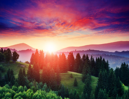 Beautiful green hills at twilight. Dramatic red sky. Carpathian, Ukraine, Europe. Beauty world. Stock Photo