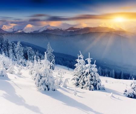monta�as nevadas: Puesta de sol en el majestuoso paisaje de monta�a invierno. El cielo dram�tico.