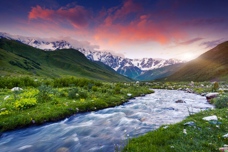 the river: Fantastic landscape and colorful overcast sky at the foot of  Mt. Shkhara. Upper Svaneti, Georgia, Europe. Caucasus mountains. Beauty world. Stock Photo