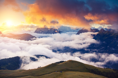 Great view of the foggy Val di Fassa valley with passo Sella. National Park. Dolomites, South Tyrol. Location Canazei, Campitello, Mazzin. Italy, Europe. Dramatic scene. Beauty world. Stockfoto