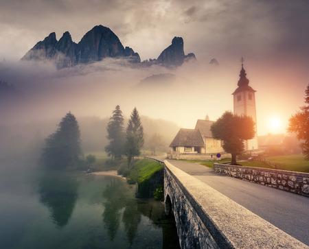 Colorido escena Majestic de niebla por la mañana en el parque nacional de Triglav, ubicada en el Valle de Bohinj de los Alpes Julianos. Espectacular vista de la iglesia de San Juan Bautista. Eslovenia, Europa. Mundo de belleza ..