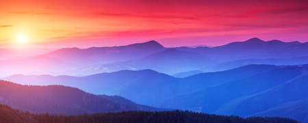 Red sunset in the mountains landscape with sunny beams. Dramatic scene in Carpathian, Ukraine 스톡 콘텐츠