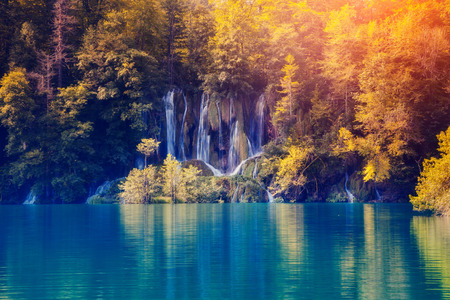 waterfall with sky: Majestic view on waterfall with turquoise water and sunny beams in Plitvice Lakes National Park. Forest glowing by sunlight. Croatia. Europe. Dramatic morning scene. Beauty world.