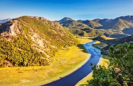 sinuous: Sinuous river flowing through mountains. Natural park. Dramatic scene. Rijeka Crnojevica. Located near Skadar Lake, Montenegro, Europe. Beauty world. Stock Photo
