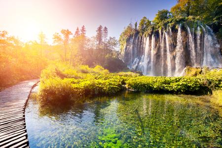 청록색 물, 플리트 비체 호수 국립 공원에서 화창한 광선 폭포 장엄한보기. 숲은 햇빛에 의해 빛나는. 크로아티아. 유럽. 극적인 아침 장면입니다.
