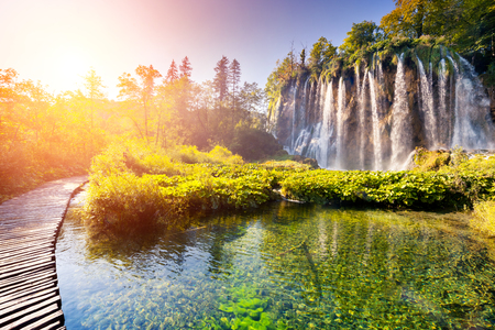 waterfall with sky: Majestic view on waterfall with turquoise water and sunny beams in Plitvice Lakes National Park. Forest glowing by sunlight. Croatia. Europe. Dramatic morning scene. Beauty world. Instagram effect.