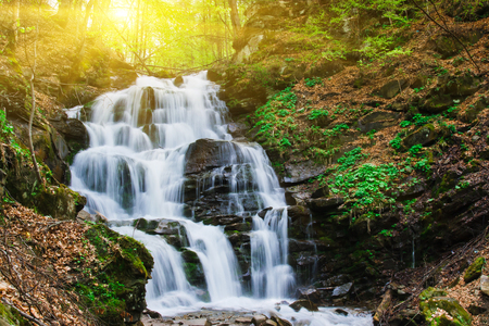 bright sky: Tranquil waterfall scenery in the middle of autumn forest