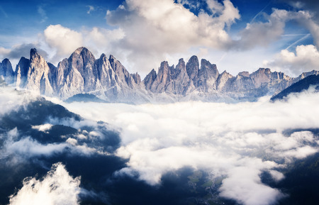 scene: Great view of the foggy Val di Fassa valley with pass Sella. National Park. Dolomites (Dolomiti), South Tyrol. Location Canazei, Campitello, Mazzin. Italy, Europe. Dramatic scene. Beauty world.