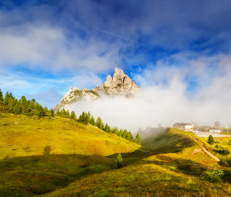 stria: Great view of the foggy Mt. Sass de Stria from Falzarego pass. National Park. Dolomites (Dolomiti), South Tyrol. Location Cortina dAmpezzo. Italy, Europe. Dramatic scene. Beauty world. Stock Photo