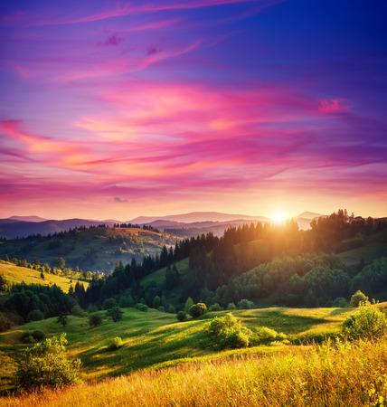 cielo: Colinas verdes hermosas brillantes por la luz del sol caliente en el crepúsculo. Escena dramática. Cielo de colores, nubes rojas. Cárpatos, Ucrania, Europa. Mundo de la belleza. Foto de archivo