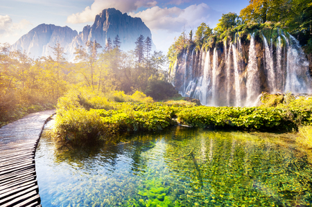 Vista maestosa sulla cascata con acqua turchese e travi di sole nel parco nazionale dei laghi di Plitvice. Foresta incandescente dalla luce solare. Croazia. Europa. scena drammatica mattina. mondo di bellezza. Archivio Fotografico