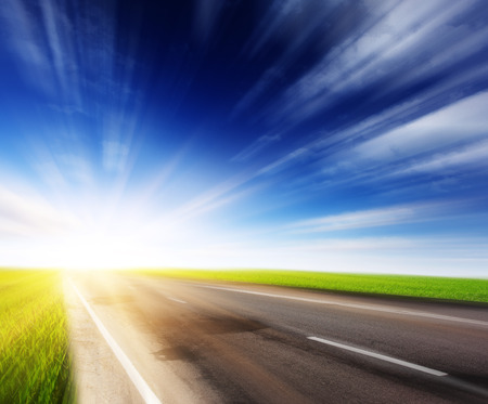 Empty asphalt blurry road with cloudy sky and sunlight Stock Photo