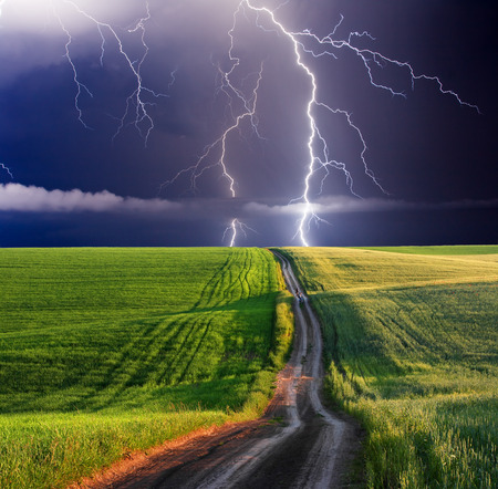 grass and sky: summer storm beginning with lightning Stock Photo