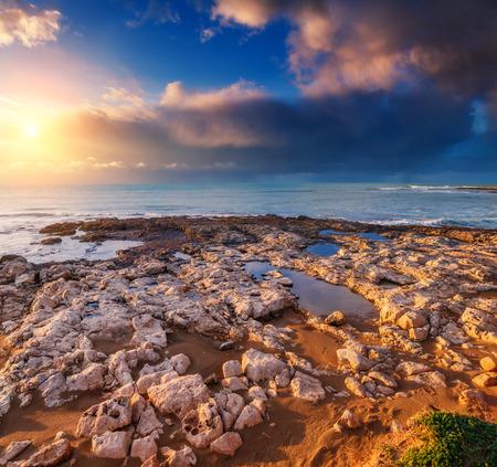sicilia: Fantastic view of the Isola delle Correnti. Located on cape Passero. Dramatic morning scene. Dark overcast sky. Sicilia, Italy, Europe. Mediterranean and Ionian sea. Beauty world.