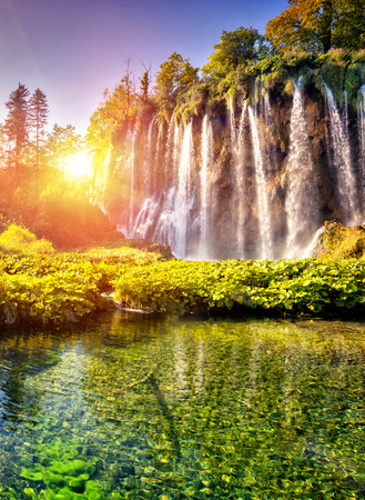 Majestic view on waterfall with turquoise water and sunny beams in Plitvice Lakes National Park in Croatia. Banco de Imagens
