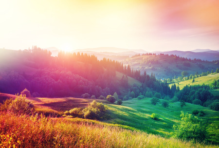 Beautiful hills glowing by sunlight at twilight. Dramatic scene. Colorful sky. Carpathian, Ukraine, Europe. Beauty world. Cross processed retro and vintage style. Instagram toning effect. Soft filter.