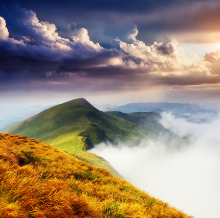 A great view of the foggy hills and cloudy sky which glowing by sunlight. Dramatic and picturesque morning scene. Location place: Carpathian, Ukraine, Europe. Artistic picture. Beauty world. Stock Photo