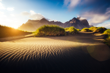 majestic mountain: Beautiful view of the yellow hills glowing by sunlight. Majestic and gorgeous scene. Location famous place Stokksnes cape, Vestrahorn (Batman Mountain), Iceland, Europe. Warm toning. Beauty world.