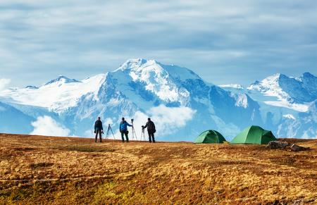 Group of photographers watching spectacular view of the snow ridge. Dramatic and picturesque scene. Location place Mkheer glacier, Mestia, Svaneti, Georgia, Europe. High Caucasus ridge. Beauty world.