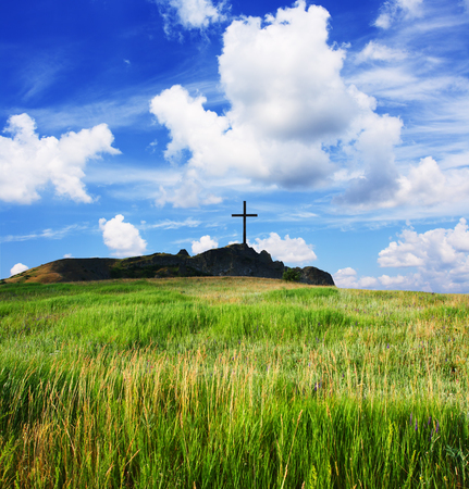Religious cross on a beautiful green hill Stock Photo