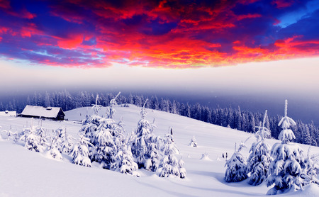Majestic sunset in the winter mountains landscape. Mountain house