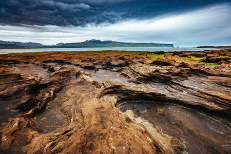 Sandy rocks with by magma formed by winds. Location Sudurland, cape Dyrholaey, south coast of Iceland, Europe.