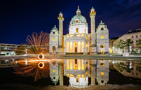 Magical evening view of the St. Charles Church (Karlskirche) and fire show. Location place Karlsplatz in Vienna. Austria, Europe.