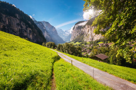 Great view of alpine village glowing by sunlight. Location place Swiss alps, Lauterbrunnen valley, Staubbach waterfall, Europe.