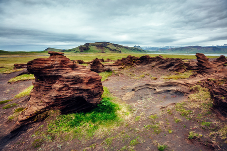 Sandy rocks with by magma formed by winds. Popular tourist attraction. Location Sudurland, cape Dyrholaey, south coast of Iceland, Europe. Banco de Imagens - 85415745