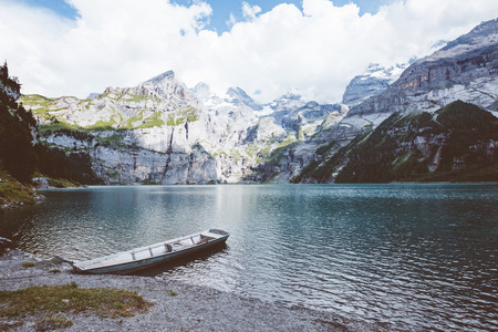 Glacier pond Oeschinensee. Popular tourist attraction. Picturesque and gorgeous scene. Location Swiss alps, Kandersteg, Bernese Oberland, Europe. Vintage effect. Stock Photo
