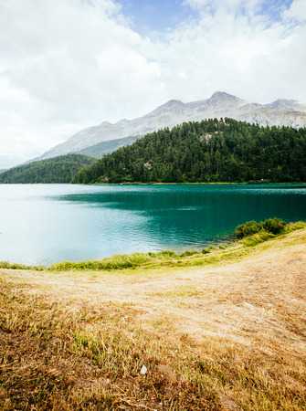 Great view of the azure pond Champfer in alpine valley. Picturesque and gorgeous scene. Location Swiss alps, Silvaplana village. Europe. Retro and vintage style. Stock Photo