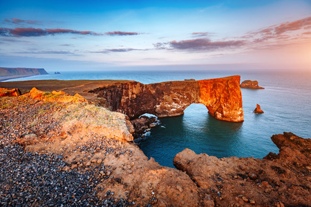 Amazing black arch of lava standing in the sea on small peninsula. Popular tourist attraction. Unusual and gorgeous scene. Location Sudurland, cape Dyrholaey, coast of Iceland