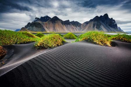 O grande vento ondulava a areia negra da praia. Cena pitoresca e linda. Atração turística popular. Local famoso lugar Stokksnes cabo, Vestrahorn (Montanha Batman), Islândia