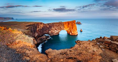 작은 반도에 바다에 서있는 용암의 놀라운 검은 아치. 인기있는 관광 명소. 비정상적이 고 화려한 장면. 위치 Sudurland, 케이프 Dyrholaey, 아이슬란드의 해 스톡 콘텐츠