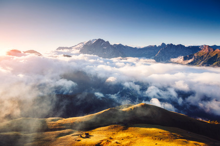 Creamy fog covered the glacier Marmolada in morning light. Great and gorgeous scene. Location place Val di Fassa valley, passo Sella, Dolomiti, Tyrol. Italy, Europe.