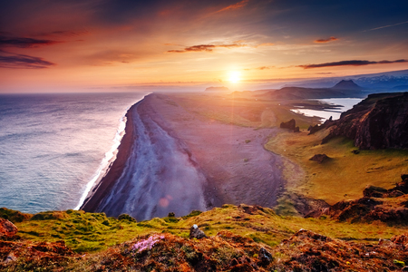 Amazing black sand of lava in the beach on small peninsula. Popular tourist attraction. Unusual and gorgeous scene. Location place Sudurland, cape Dyrholaey, coast of Iceland, Europe.