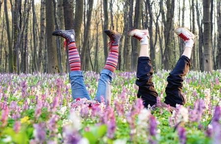 Two girls lying upside down in blooming meadow.