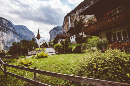 Great view of alpine village. Gorgeous scene. Location place Swiss alp, Lauterbrunnen valley, Staubbach waterfall, Europe. Cross process, retro and vintage style