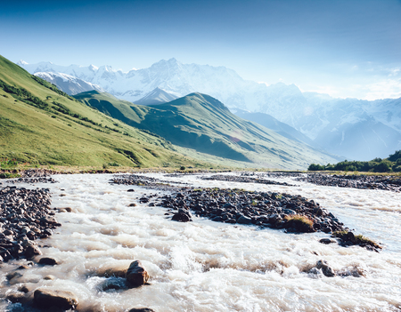 Rapid river at the foot of the glacier Shkhara. Picturesque and gorgeous scene. Location place Svaneti, Mestia, Georgia, Europe. High Caucasus ridge. Vintage effect