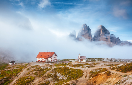 Great foggy view of the National park Tre Cime di Lavaredo with rifugio Locatelli. Dramatic and gorgeous scene. Location famous place Dolomiti alps, South Tyrol, Auronzo, Italy, Europe. Beauty world. Stock Photo
