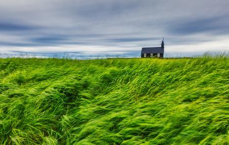 Lonely Budakirkja christian church sits among a field of lava rock. Dramatic scene. Popular tourist attraction. Location place hamlet of Budir, Snafellsnes peninsula Iceland, Europe. Beauty world.