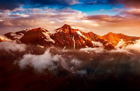 A look at the sunlit hills at twilight. Dramatic evening scene. Location place Grossglockner High Alpine Road, Austria. Europe. Climate change. Drone photography. Explore the worlds beauty.