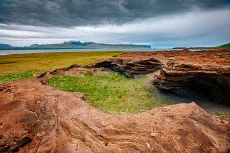 Red sandy rock with by magma formed by wind. Popular tourist attraction. Unusual and gorgeous scene. Location place Sudurland, cape Dyrholaey coast of Iceland, Europe. Artistic picture. Beauty world.