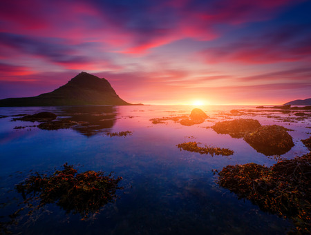 Evening Kirkjufell volcano the coast of Snaefellsnes peninsula. Location Kirkjufellsfoss. Typical Icelandic scene. Unique place on earth. Wonderful image of wallpaper. Explore the worlds beauty.