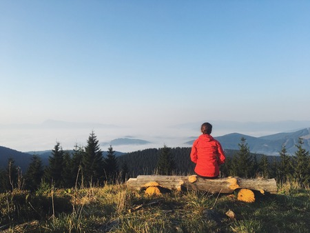 A girl in a red jacket watching the sunrise on the mountain top. Dramatic and gorgeous scene. Location Carpathian, Ukraine, Europe. Beauty world. Mobile photography. 版權商用圖片