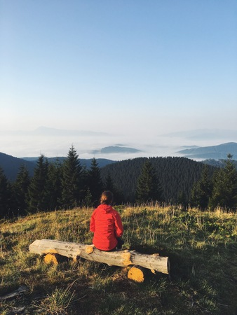 A girl in a red jacket watching the sunrise on the mountain top. Dramatic and gorgeous scene. Location Carpathian, Ukraine, Europe. Beauty world. Mobile photography. Banco de Imagens