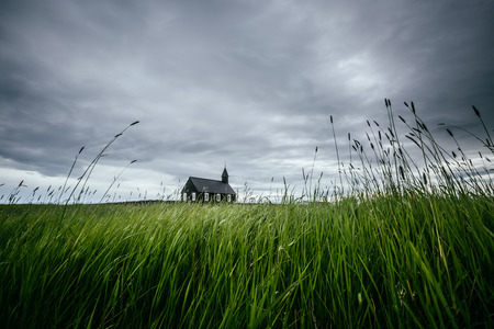 Scenic image of lonely Budakirkja christian church. Location hamlet of Budir, Snafellsnes peninsula, Iceland, Europe. Great picture of wild area. Excellent wallpapers. Discover the beauty of earth. Фото со стока - 114090801