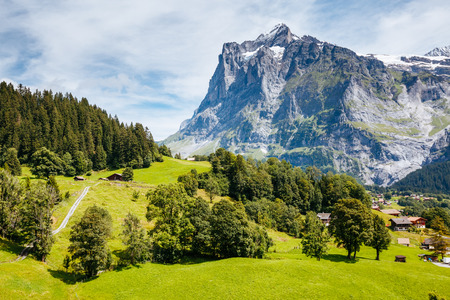 Sunny view of alpine Eiger village. Picturesque scene. Popular tourist attraction. Location place Swiss alps, Grindelwald valley in the Bernese Oberland, Europe. Drone photography. Beauty world.